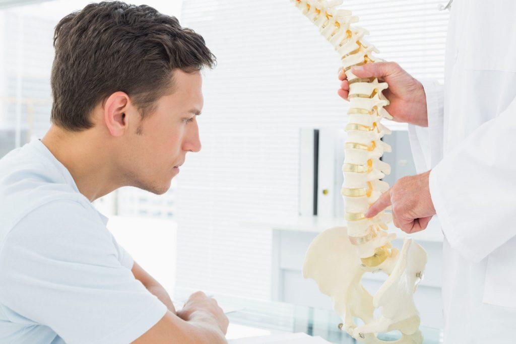 fysioterapeut viser patient hvor problemer sidder i rygsøjlen